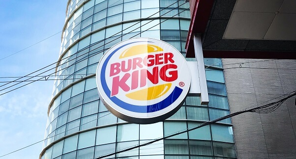 Shining Burger King logo hanging at the side of a Burger King restaurant