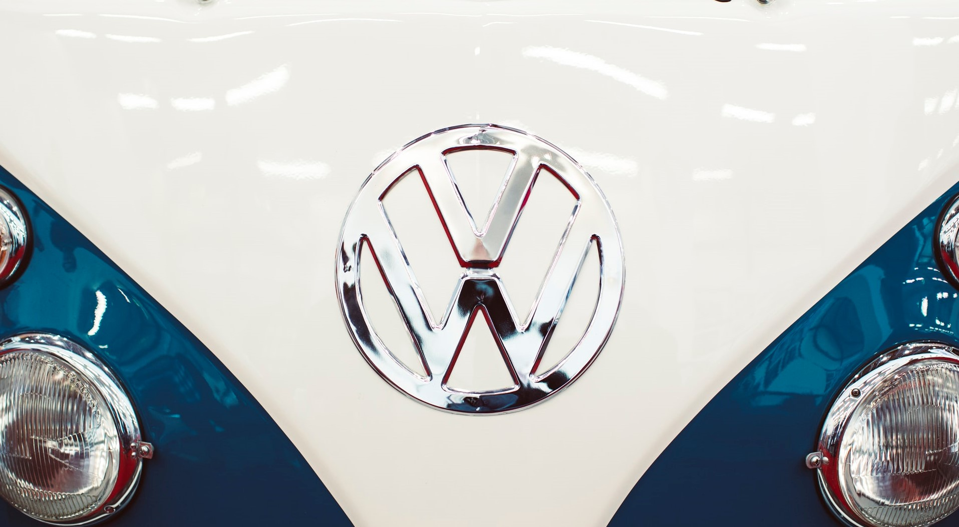 The shiny Volkswagen logo emblem on a VW bus